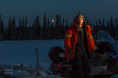 Ski trails manager Jason Garron takes a break on frozen Smith Lake while grooming the skate ski track on the UAF trails early on a cold February morning.  Filename: CAM-16-4818-43.jpg