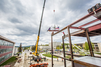 Iron workers with Davis Constructors prepare to place the final steel beam into position in UAF's new engineering facility this afternoon while a crowd of university, legislative and business leaders look on. The final piece of steel is topped with Alaska and U.S. flags and, following an ancient  Scandinavian tradition, a small tree.  Filename: CAM-14-4199-108.jpg