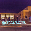 "Student volunteers walk in and out of the Patty Center during a late night promotional multi-media production introducing the Nanook Nation theme.  <div class=""ss-paypal-button"">Filename: CAM-13-3925-136.jpg</div><div class=""ss-paypal-button-end"" style=""""></div>"