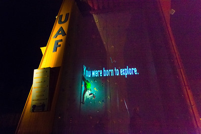 A video image is projected on UAF's outdoor climbing wall while a student climber makes his way up the route during a late night promotional multi-media production.  Filename: CAM-13-3925-103.jpg