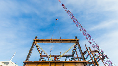 A 220-foot crane lowers steel beams into position as workers secure it during construction of the new engineering facility on the Fairbanks campus in April, 2014.  Filename: CAM-14-4131-31.jpg