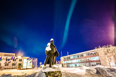 A strand of light from the aurora borealis floats above the statue of Charles Bunnell and the Bunnell Building on the Fairbanks campus.  Filename: CAM-13-3724-17.jpg