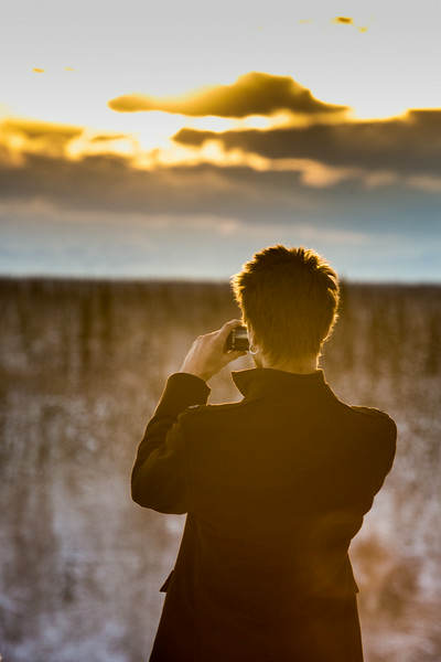 """A student pauses to snap a photo of a January sunset on the Fairbanks campus.  <div class=""""ss-paypal-button"""">Filename: CAM-14-4039-80.jpg</div><div class=""""ss-paypal-button-end""""></div>"""