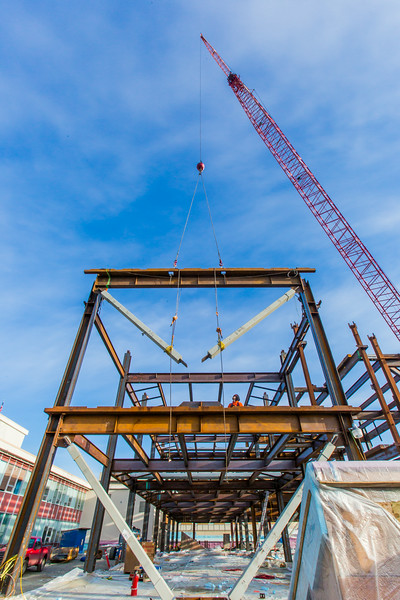"""A 220-foot crane lowers steel beams into position as workers wait to attach it during construction of the new engineering facility on the Fairbanks campus in April, 2014.  <div class=""""ss-paypal-button"""">Filename: CAM-14-4131-26.jpg</div><div class=""""ss-paypal-button-end""""></div>"""