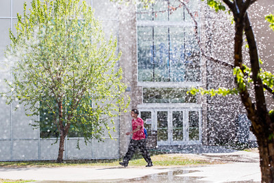A student walks in front of the Duckering Building while Facility Services waters the lawns with sprinkler systems around campus Wednesday morning.  Filename: CAM-12-3421-83.jpg