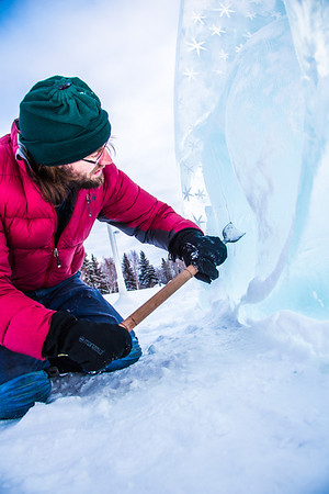 Ronald Daanen, a research assistant professor with UAF's Institute of Northern Engineering, puts some finishing touches on an ice carving of a hibernating bear in front of the University of Alaska Museum of the North Monday afternoon.  Filename: CAM-13-3701-6.jpg