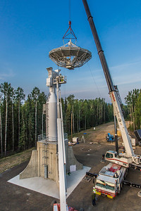 A crew from Texas helps install an 11-meter antenna operated by UAF's Alaska Satellite Facility at its location on West Ridge. Once fully operational, the dish will gather data from spacecraft about land surface, biosphere, atmosphere, oceans and outer space. It's one of several strategically placed antennas that can capture data from polar-orbiting satellites several times per day.  Filename: CAM-13-3903-040.jpg