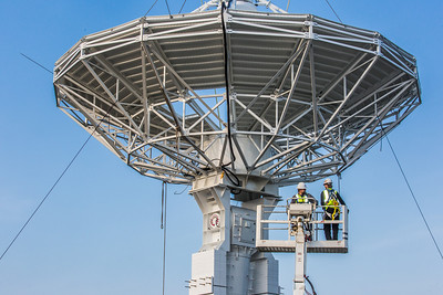 A crew from Texas helps install an 11-meter antenna operated by UAF's Alaska Satellite Facility at its location on West Ridge. Once fully operational, the dish will gather data from spacecraft about land surface, biosphere, atmosphere, oceans and outer space. It's one of several strategically placed antennas that can capture data from polar-orbiting satellites several times per day.  Filename: CAM-13-3903-074.jpg