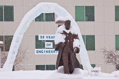 The traditional ice arch, designed and built each year by students in UAF's civil engineering program, stands behind the statue of Charles Bunnell on a snowy March afternoon.  Filename: CAM-12-3320-12.jpg
