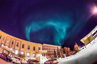 The aurora borealis floats above Signers' Hall, the Gruening Building and the rest of the Fairbanks campus.  Filename: CAM-13-3724-37.jpg