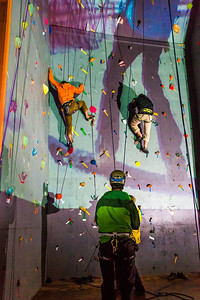 A video image is projected on UAF's outdoor climbing wall while a pair of student climbers make their up the route during a late night promotional multi-media production.  Filename: CAM-13-3925-63.jpg