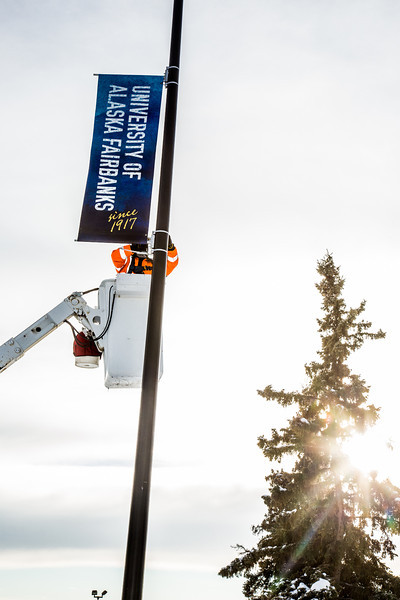 """A crew from UAF's Facilities Services monts new banners at various locations on the Fairbanks campus.  <div class=""""ss-paypal-button"""">Filename: CAM-13-3722-23.jpg</div><div class=""""ss-paypal-button-end"""" style=""""""""></div>"""