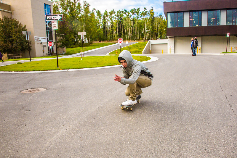 """A skateboarder zooms down the hill in front of Wood Center during Orientation Week on the Fairbanks campus at the start of the fall 2015 semester.  <div class=""""ss-paypal-button"""">Filename: CAM-15-4638-081.jpg</div><div class=""""ss-paypal-button-end""""></div>"""