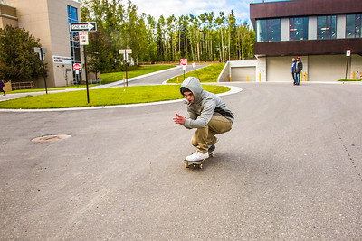A skateboarder zooms down the hill in front of Wood Center during Orientation Week on the Fairbanks campus at the start of the fall 2015 semester.  Filename: CAM-15-4638-081.jpg