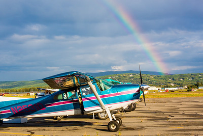 A rainbow appears behind a small plane as it awaits takeoff from the Fairibanks International Airport on a summer morning.  Filename: CAM-12-3497-016.jpg