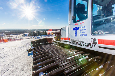 The sun shines on the UAF terrain park's snow groomer on a late afternoon.  Filename: CAM-14-4088-46.jpg