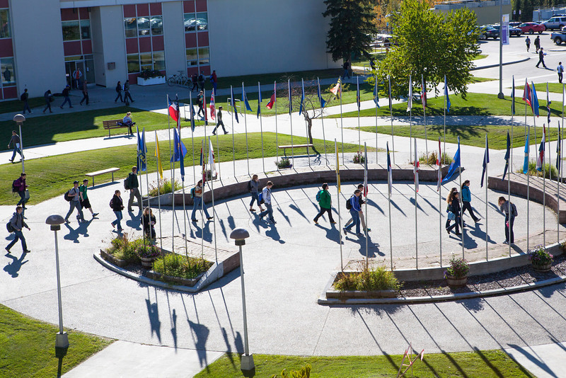 """Students finished with their class in the Bunnell building walks accross the Circle of Flags on a September afternoon.  <div class=""""ss-paypal-button"""">Filename: CAM-12-3543-3.jpg</div><div class=""""ss-paypal-button-end"""" style=""""""""></div>"""