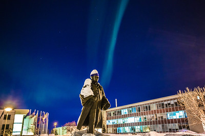 A strand of light from the aurora borealis floats above the statue of Charles Bunnell and the Bunnell Building on the Fairbanks campus.  Filename: CAM-13-3724-15.jpg
