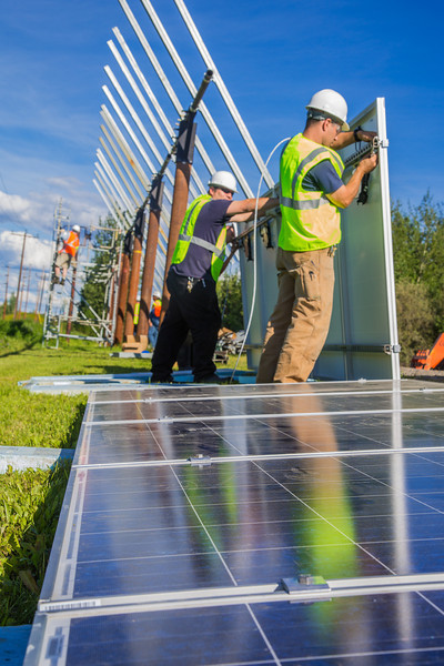 """Students in a class on solar photovoltaic design and installation prepare to mount solar panels along the road near the Cold Climate Housing Research Center  near the Fairbanks campus. The class is offered through UAF's Community and Technical College.  <div class=""""ss-paypal-button"""">Filename: CAM-12-3467-17.jpg</div><div class=""""ss-paypal-button-end"""" style=""""""""></div>"""