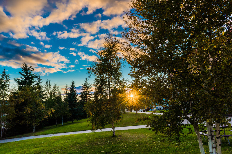 """The setting sun bursts through the trees in front of Lathrop Hall on the Fairbanks campus during Orientation Week at the start of the fall 2015 semester.  <div class=""""ss-paypal-button"""">Filename: CAM-15-4638-098.jpg</div><div class=""""ss-paypal-button-end""""></div>"""