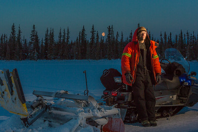 Ski trails manager Jason Garron takes a break on frozen Smith Lake while grooming the skate ski track on the UAF trails early on a cold February morning.  Filename: CAM-16-4818-44.jpg