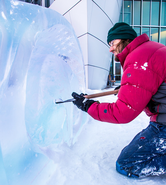 """Ronald Daanen, a research assistant professor with UAF's Institute of Northern Engineering, puts some finishing touches on an ice carving of a hibernating bear in front of the University of Alaska Museum of the North Monday afternoon.  <div class=""""ss-paypal-button"""">Filename: CAM-13-3701-15.jpg</div><div class=""""ss-paypal-button-end"""" style=""""""""></div>"""