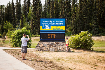 People stop for a photo as the temperature reached 90 degrees at the time and temperature sign in late June 2013 on campus.  Filename: CAM-13-3868-23.jpg