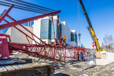 Workers assemble the pieces of a 220-foot crane used to install steel beams on the new expansion of the Duckering Building.  Filename: CAM-14-4122-24.jpg