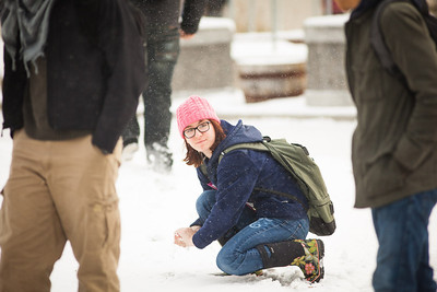With a snowball on hand, Justine Webb, eyes her friends as a perfect target at the Cornerstone Plaza during the first snowfall of the semester in mid-October 2012.  Filename: CAM-12-3589-88.jpg