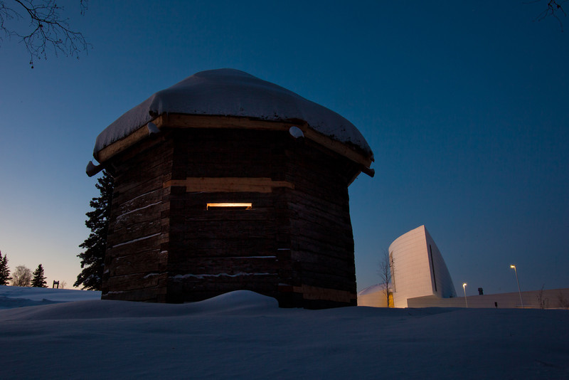 """The 1841 Russian blockhouse stands at first light on its new foundation near the University of Alaska Museum of the North. It was the first structure built by the Russian-American Company at Kolmakovsky Redoubt near Aniak. It is one of the oldest Russian-era structures in Alaska. In 1929, the blockhouse was disassembled and moved to Fairbanks where last summer a preservation team completed work on reattaching an updated roof outfitted with tundra sod and tamarack poles.  <div class=""""ss-paypal-button"""">Filename: CAM-12-3277-05.jpg</div><div class=""""ss-paypal-button-end"""" style=""""""""></div>"""
