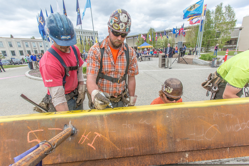 """Iron workers with Davis Constructors sign their names on the final steel beam before it's lifted into position in UAF's new engineering facility following a brief ceremony May 22. The final piece of steel is topped with Alaska and U.S. flags and, following an ancient  Scandinavian tradition, a small tree.  <div class=""""ss-paypal-button"""">Filename: CAM-14-4199-84.jpg</div><div class=""""ss-paypal-button-end""""></div>"""