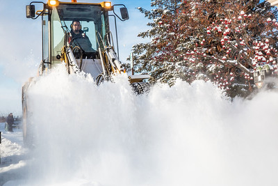 A Facilities Services crew member uses some heavy equipment to sweep the sidewalk in front of Signers' Hall after a late winter snowfall.  Filename: CAM-13-3786-6.jpg