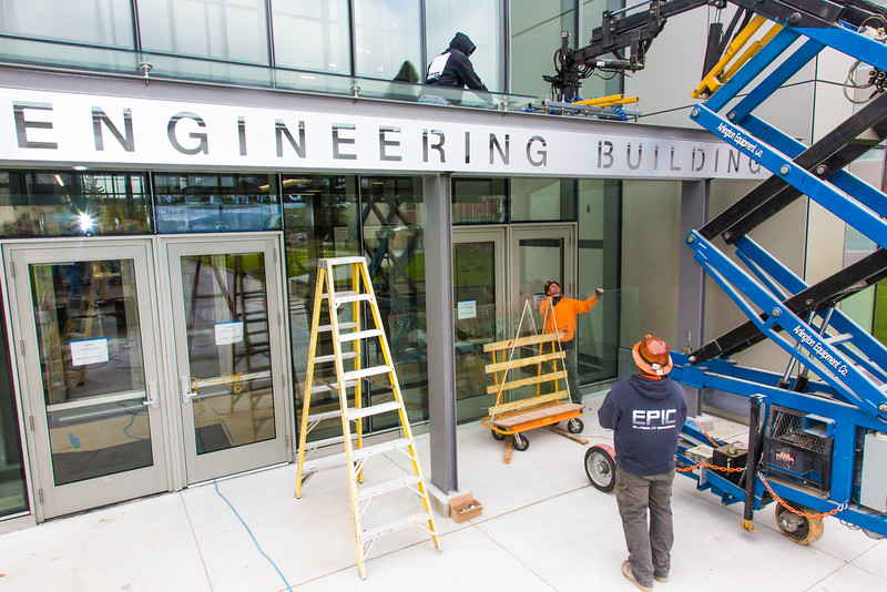 """A crew from Hoffer Glass installs panels on the entry way to the new engineering building on the Fairbanks campus in August 2015.  <div class=""""ss-paypal-button"""">Filename: CAM-15-4634-024.jpg</div><div class=""""ss-paypal-button-end""""></div>"""