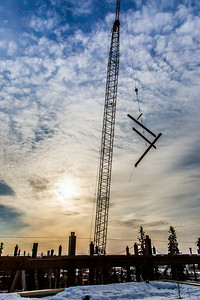 A 220-foot crane lifts steel beems into position as workers complete the superstructure for the third floor of the new engineering facility in April 2014.  Filename: CAM-14-4131-44.jpg