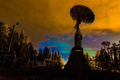 A faint glow of northern lights appears in the eastern sky beyond the newly installed 11-antenna operated by UAF's Alaska Satellite Facility. Once fully operational, the dish will gather data from spacecraft about land surface, biosphere, atmosphere, oceans and outer space. It's one of several strategically placed antennas that can capture data from polar-orbiting satellites several times per day.  Filename: CAM-13-3940-9.jpg