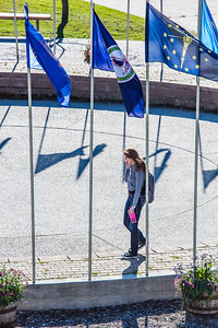 A student walks through the circle of flags in Cornerstone Plaza on the Fairbanks campus.  Filename: CAM-12-3541-37.jpg