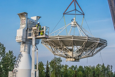 A crew from Texas helps install an 11-meter antenna operated by UAF's Alaska Satellite Facility at its location on West Ridge. Once fully operational, the dish will gather data from spacecraft about land surface, biosphere, atmosphere, oceans and outer space. It's one of several strategically placed antennas that can capture data from polar-orbiting satellites several times per day.  Filename: CAM-13-3903-031.jpg
