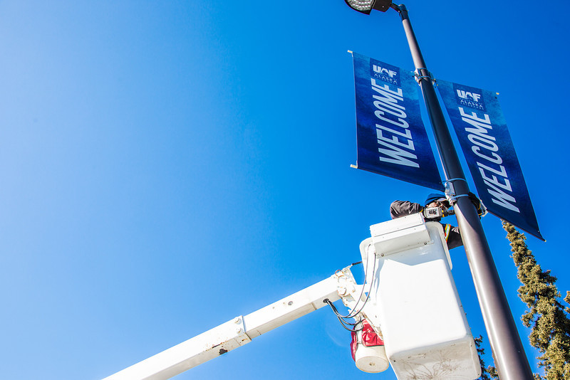 "A facilities services crew member installs new welcome banners to a light pole near UAF's Farmers' Loop Road entrance.  <div class=""ss-paypal-button"">Filename: CAM-13-3779-3.jpg</div><div class=""ss-paypal-button-end"" style=""""></div>"