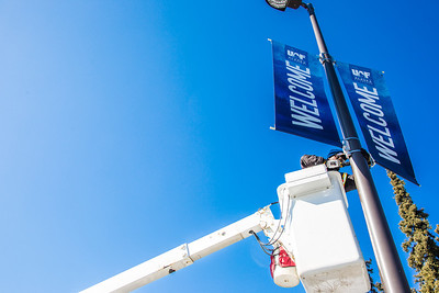 A facilities services crew member installs new welcome banners to a light pole near UAF's Farmers' Loop Road entrance.  Filename: CAM-13-3779-3.jpg