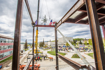 Iron workers with Davis Constructors secure the final steel beam into position in UAF's new engineering facility this afternoon while a crowd of university, legislative and business leaders look on. The final piece of steel is topped with Alaska and U.S. flags and, following an ancient  Scandinavian tradition, a small tree.   Filename: CAM-14-4199-119.jpg