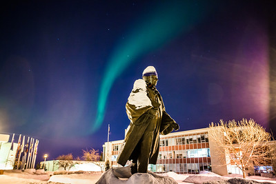 A strand of light from the aurora borealis floats above the statue of Charles Bunnell and the Bunnell Building on the Fairbanks campus.  Filename: CAM-13-3724-11.jpg