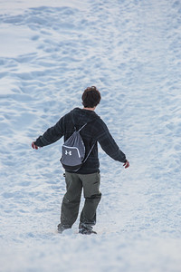 A student slides down the hill by the Patty Center during a warm January afternoon on the Fairbanks campus.  Filename: CAM-14-4039-90.jpg