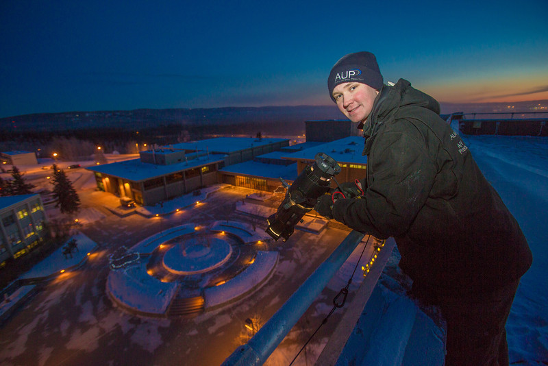 """Jon Huff with AUP mounts and adjusts the light projecting the """"Naturally Inspiring"""" tagline down on the campus from atop the Gruening Building on a cold November morning.  <div class=""""ss-paypal-button"""">Filename: CAM-12-3665-19.jpg</div><div class=""""ss-paypal-button-end"""" style=""""""""></div>"""