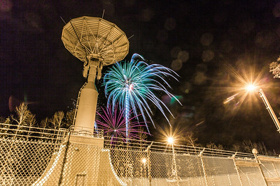 Fireworks illuminate the Alaska Satellite Facility's 11-meter antenna on West Ridge during the annual New Year's Eve Sparktacular.  Filename: CAM-13-4028-46.jpg