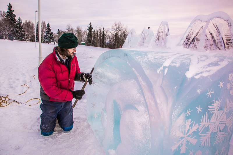 """Ronald Daanen, a research assistant professor with UAF's Institute of Northern Engineering, puts some finishing touches on an ice carving of a hibernating bear in front of the University of Alaska Museum of the North Monday afternoon.  <div class=""""ss-paypal-button"""">Filename: CAM-13-3701-23.jpg</div><div class=""""ss-paypal-button-end"""" style=""""""""></div>"""