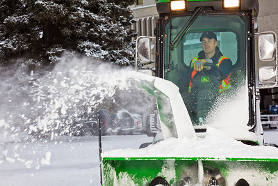 Paul Dick, an equipment operator for Facilities Services, blows snow from a campus sidewalk after a November dusting.  Filename: CAM-11-3213-15.jpg