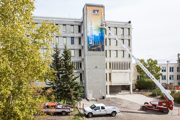 """Construction workers attach a banner on the side of the Gruening Building.  <div class=""""ss-paypal-button"""">Filename: CAM-13-3921-41.jpg</div><div class=""""ss-paypal-button-end"""" style=""""""""></div>"""