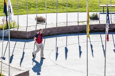A student walks through the circle of flags in Cornerstone Plaza on the Fairbanks campus.  Filename: CAM-12-3541-21.jpg