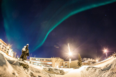 A strand of light from the aurora borealis floats above the statue of Charles Bunnell and the Bunnell Building on the Fairbanks campus.  Filename: CAM-13-3724-18.jpg