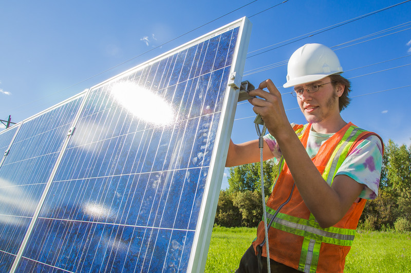 """Alexander Bergman attaches mounting hardware to the back of a solar panel being installed along the road near the Cold Climate Housing Research Center as part of his class in solar photovoltaic design being offered through UAF's Community and Technical College.  <div class=""""ss-paypal-button"""">Filename: CAM-12-3467-08.jpg</div><div class=""""ss-paypal-button-end"""" style=""""""""></div>"""